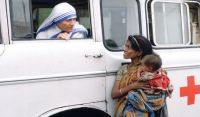 Mother Teresa talking with a poor woman and her child from a Red Cross minibus in Calcutta, India. Photo: AFP